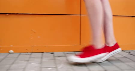 red shoes : Girl walk on tiptoes in front of orange wall as street workout. Focus on her feet in red sneakers