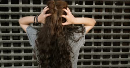 perimeter : Cute Girl Comb Her Long Hair By Hands Rear View In The Street In Front Of Metal Fence