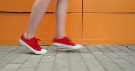 locomotion : Girls Legs In red Trainers. Run Along The Orange Wall Ground Level Shot.
