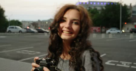 ha : Hipster girl with vintage film camera smiling in the street looking at camera