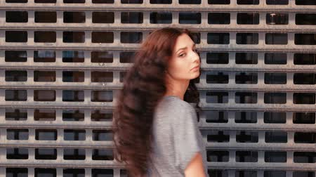 perseguição : Long haired woman turn back and smile in front of metal grid or mesh