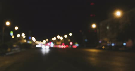 xenon lights : Defocused night traffic lights. Bluured cars lights dividing in two streams, pan left 4k footage