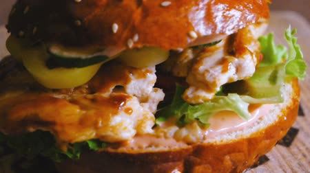 borjúhús : Tasty burger with fryed chicken meat onion cucumber and lettuce turning in slow motion closeup footage Stock mozgókép
