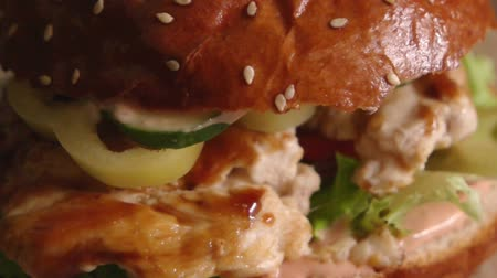 borjúhús : Burger with fryed chicken meat lying on tomatoes cucumber and lettuce turning slow motion 120 fps footage