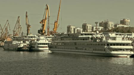mooring : Many Moored River Cruise Boats In Front of Port Cranes Defocused Footage