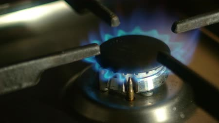 gazprom : Putting pan off then on gas fire of stove closeup shot