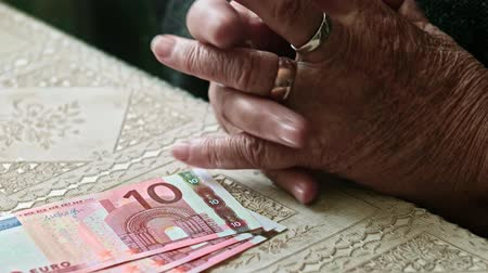 mínimo : Hands of senior woman on table with some euro banknotes on closeup 4k footage Stock Footage