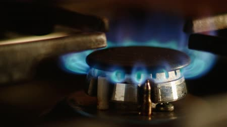gazprom : Close up on the flame Natural gas in stove burner. Gas burning in a kitchen gas stove side view 4k footage