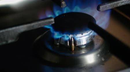 gazprom : Turning on the cooktop gas cooker. Natural gas inflammation in stove burner, close up view. Gas burning in a kitchen gas stove 4k footage Stock Footage