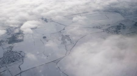 sąsiadka : View from aircraft window at earth covered with snow with clouds of fog flying over Wideo