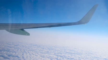 fidedigno : Wing of aircraft flying over cloud cover, view through dirty window