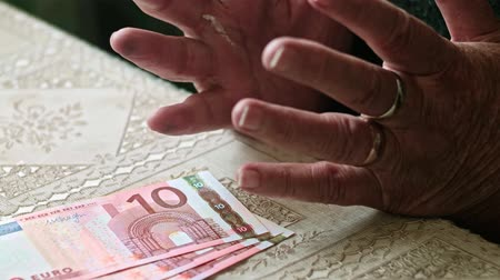 mínimo : Cost of living of senior sitizens, hands of senior woman on table with some euro banknotes on