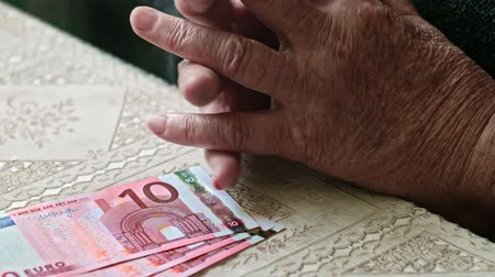 mínimo : Minimum pension concept, Hands of senior woman nervously playing with fingers and three ten euro banknotes on table
