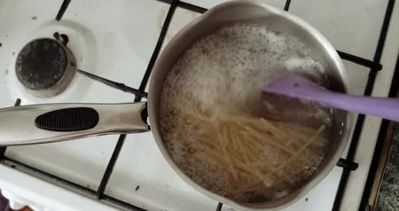 лапша : Boiling Pasta. A saucepan of boiling pasta on a gas burner in kitchen Стоковые видеозаписи