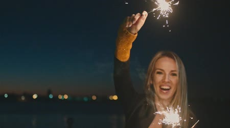 тусклый : Overhappy woman dancing with burning bengal lights in the night celebrating New Year Eve In Slow Motion