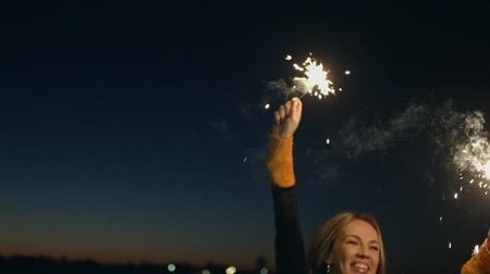 Навидад : Beautiful woman dancing while holding sparkler. Beautiful blond hair woman holding sparklers in front of night sky and celebrating New Year Eve in slow motion
