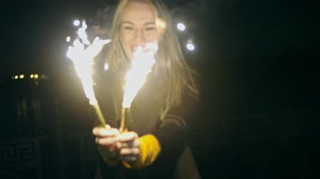 candid laughter : Woman with two sparkler. Blurred woman with burning sparkler on dark background with lights in slow motion Stock Footage