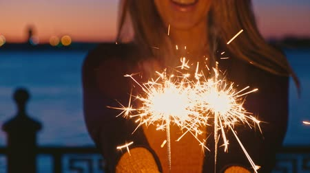 candid laughter : Woman hand holding sparkler outdoors in front of river and sunset sky Stock Footage