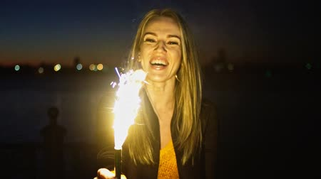 candid laughter : Overhappy woman looking at burning Roman Candle in her hadns in slow motion, blurry footage