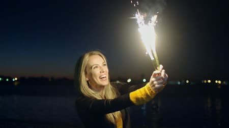 miraculous : Overhappy woman with two roman candles in her hands moving in slow-motion celebrating some kind of holiday