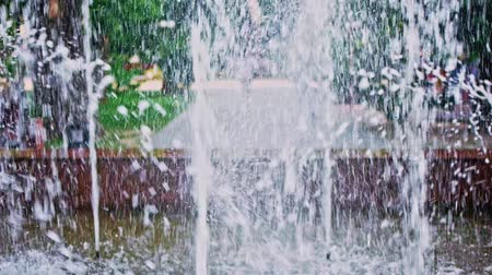 ambientalmente : Fountain slow-motion wih blurred park with walking passers-by on background