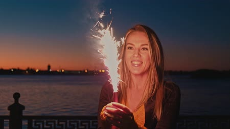 тусклый : Blonde woman having fun with a roman candle sparkler in the night.