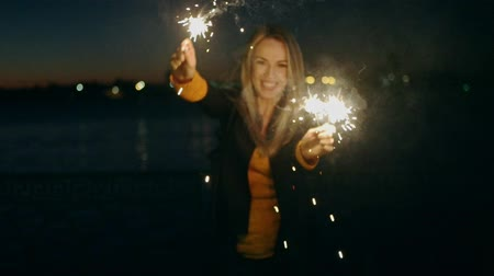 candid laughter : Cheerful woman holding two burning sparklers in hands and dancing outdoor Blond girl celebrating new year s eve with bengal lights Beautiful woman holding a sparkling sticks at party night slow motion Stock Footage