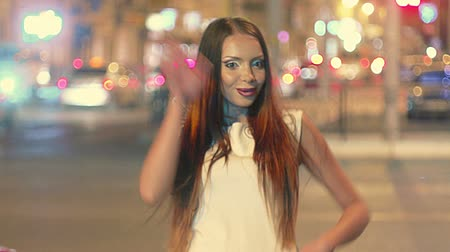 pintinho : Beautiful young woman in night city saying hello to camera with many blurred traffic lights on background
