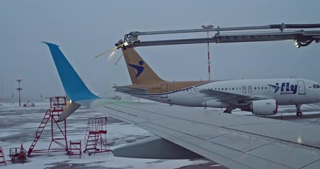 анти : Saint-Petersburg Russia, 03 March 2019: Preparing airliner for winter flight in Pulkovo Airport Covering wing with green marker means anti-frost processing have done.