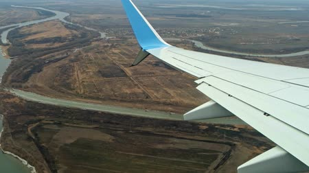canto : Astrakhan Russia 03 March 2019: Aircraft belonging to Pobeda-airlines the only lowcoster on Russian market flying over rural area with river landscape Stock Footage