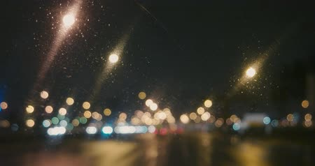 hátsó megvilágítású : Many blurred city lights on the night road in rainy weather view from inside of the car