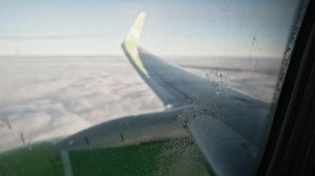 wandering : View at airplane wing and cloud cover through window with small drops of water and some dirt on surface Stock Footage