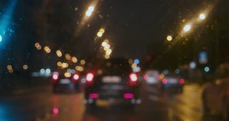 wiper : Slow moving cars with rear light on in the rain look through wet window of the car Stock Footage