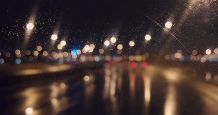 Blurred lights of night freeway through windshield front window with working wiper 影像素材