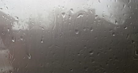 Wet window of the car in rain storm in the nightfall city