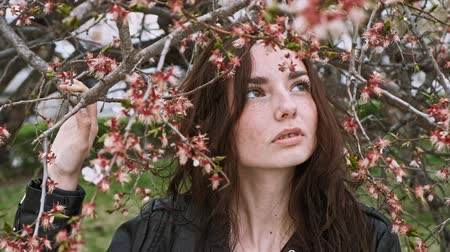 Cute girl posing with branches of blooming cherry tree obout her face in public park