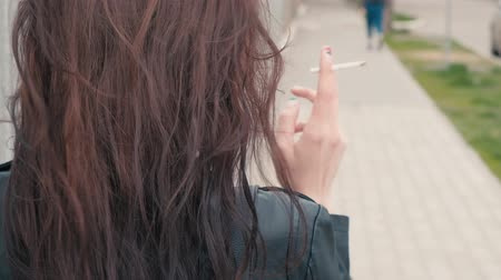 hátsó megvilágítású : Back side view of a beautiful young girl with long brown hair having a cigarette outside. A pretty young brunette with long hair smoking in the street in windy weather closeup real-time footage Stock mozgókép