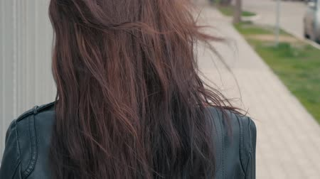 посетитель : Rear view of a beautiful young girl with long brown hair having a cigarette outside. A pretty young brunette with long hair smoking in the street in windy weather closeup real-time footage