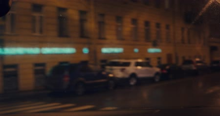 inside bus : defocused night city, the car is turning right on wet street Stock Footage