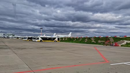 işlemek : Moskow Russia, 22 Aug 2019: Vnukovo airfield with airplanes and shuttle buses, shot through shuttle bus window with light reflections Stok Video
