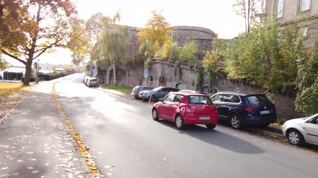Bonn Germany, 06 November 2019: small red car riding in the street while many cars parked on sidewalk of Rhine embankment 4k 50fps clip