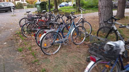 homály : Bonn Germany, 10 November 2019: Bicycles parked along the sidewalk 4k 50fps Stock mozgókép