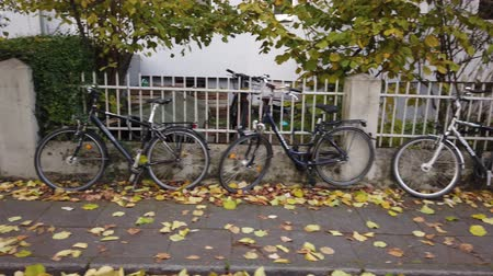 прокат : Bonn Germany, 10 November 2019: Bicycles parked leaning the fence along the sidewalk 4k 50fps. Стоковые видеозаписи