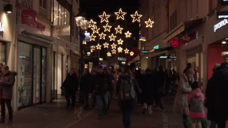 Bonn Germany, November 23 2019: Christmas fair, pedestrians walking in the decorated street in the night clip