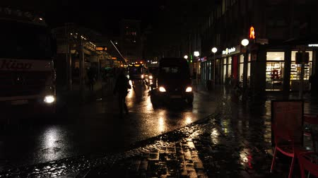 Bonn Germany, November 23 2019: View at bus stop in rainy night with buses and pedestrians 4k 50fps clip footage. 影像素材