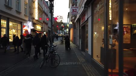 снежинки : Bonn Germany, 30 November 2019: Decorated for Christmas street in the center of Bonn City. People walking in the Christmas Market street one of the most representative historical centers of Germanys cityes hyperlapse clip Стоковые видеозаписи