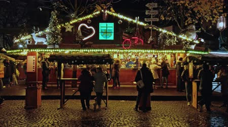 Bonn, Germany - 14 of Dec., 2019: Christmas market in the nighttime, people eating xmas snakes in the illuminated kiosk while other people walk by