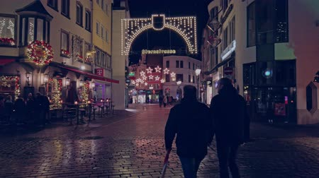szenteste : Bonn, Germany - 14 of Dec., 2019: Christmas market in the nighttime. People walk along the decorated street for Christmas 4k 60 fps slowmotion.