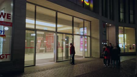 Bonn, Germany - 14 of Dec., 2019: exterior of the entrance of REWE supermarket in Bonn panning across it. Dostupné videozáznamy