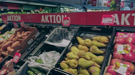 Bonn, Germany - 14 of Dec., 2019: interior shot of REWE supermarket in Bonn POV view. Shelves with fruit on sale 4k 60 fps slow motion 影像素材